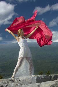 Female dancer in white dress waving red fabric in the wind on summit of Mt. Kearsarge, NH.